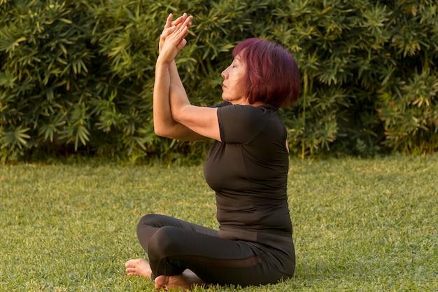 Mulher sentada na posição de ioga e fazendo exercícios de braços