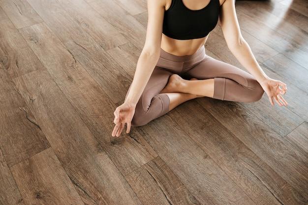 Mulher sentada na posição de lótus e meditando no estúdio de yoga