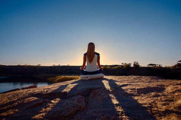 Mulher sentada na posição de lótus na rocha acima do mar e meditando. yoga ao ar livre. pôr do sol.