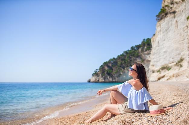 Mulher sentada na praia, aproveitando as férias de verão, olhando para o mar