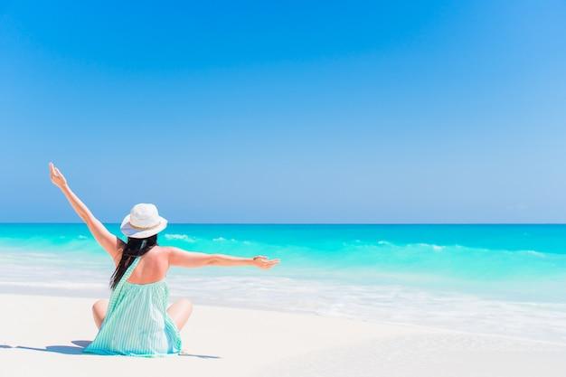Mulher sentada na praia, aproveitando as férias de verão