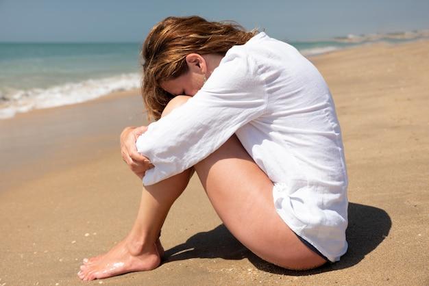Mulher sentada na praia cobrindo o rosto com as pernas