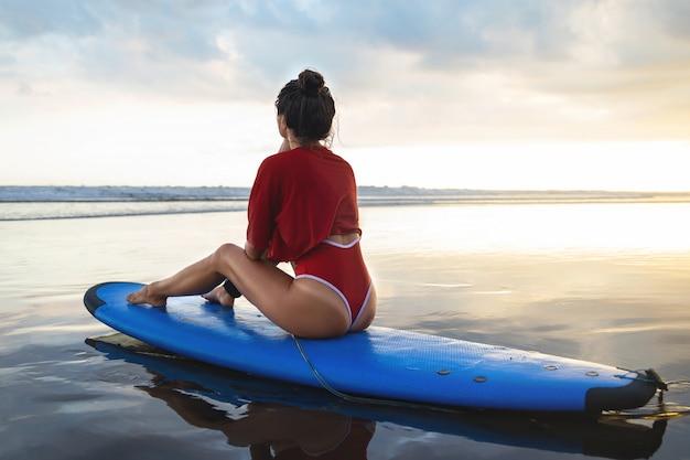 Mulher sentada na prancha de surf na praia após a sessão de surf