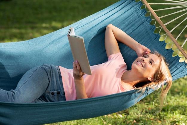 Mulher sentada na rede e segurando um livro no alto