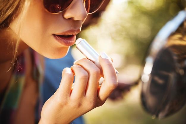 Mulher sentada na scooter ao ar livre, fazendo maquiagem de lábios.