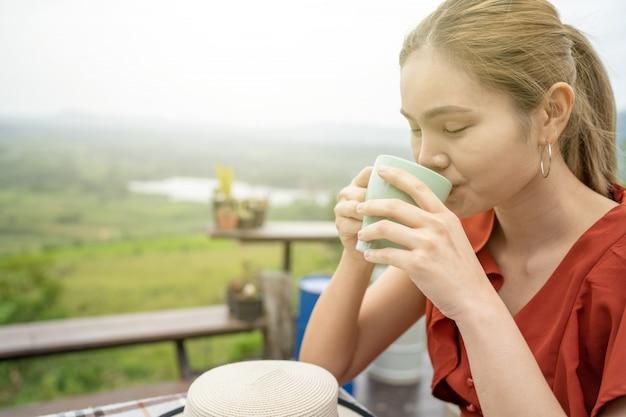 Mulher sentada na varanda com vistas naturais e tomando café