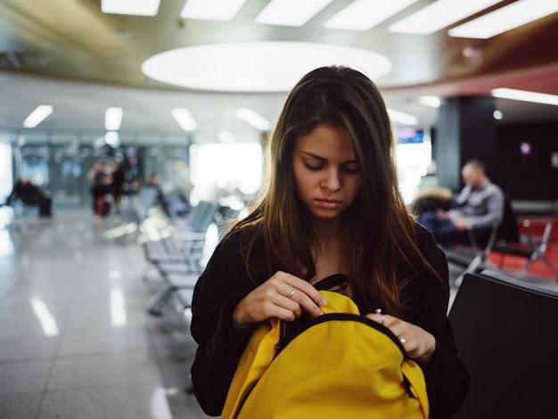Mulher sentada no aeroporto com mochila amarela esperando