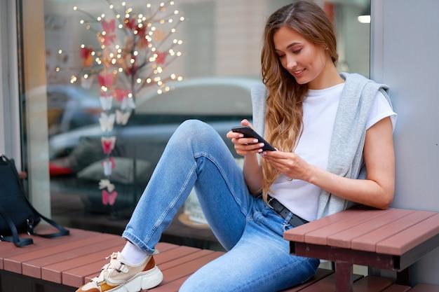 Mulher sentada no banco com smartphone