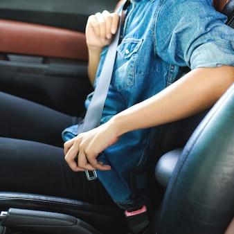 Mulher sentada no banco do carro e cinto de segurança de fixação