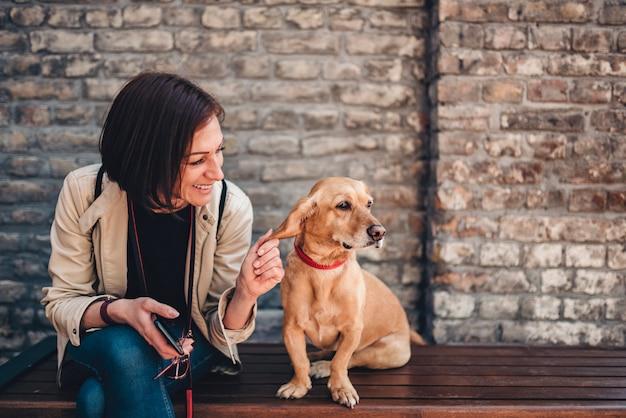 Mulher sentada no banco e acariciando seu cachorro
