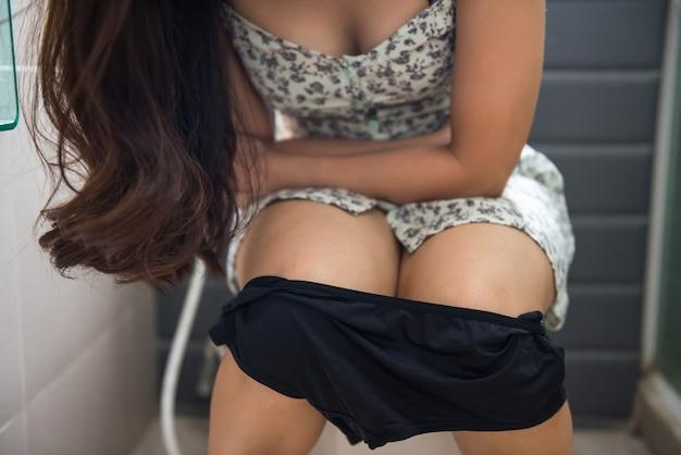 Mulher sentada no banheiro e segurando o estômago dolorido devido a forte dor de estômago, diarréia, constipação ou período de menstruação. conceito de saúde e médico. concentre-se na calcinha.