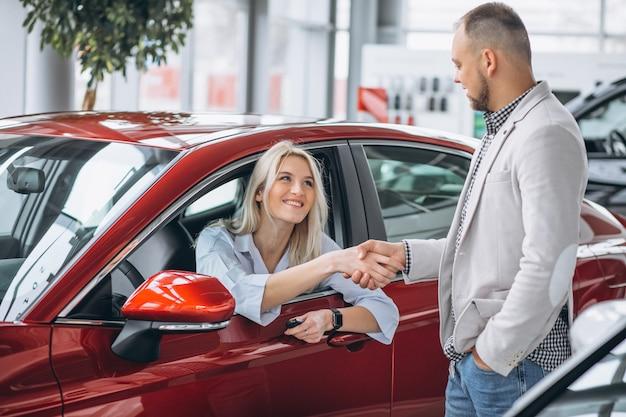 Mulher sentada no carro e receber chaves