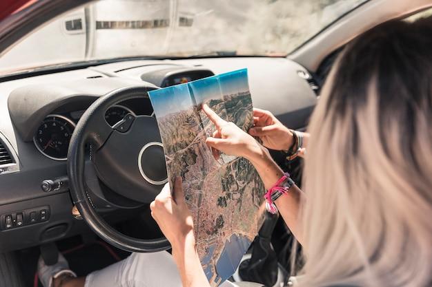 Mulher sentada no carro, mostrando o mapa para sua amiga
