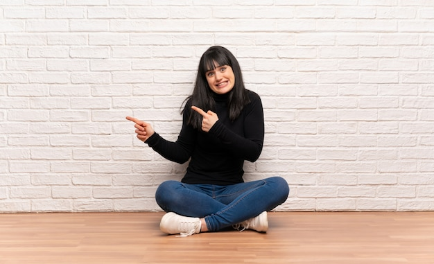 Mulher sentada no chão assustada e apontando para o lado