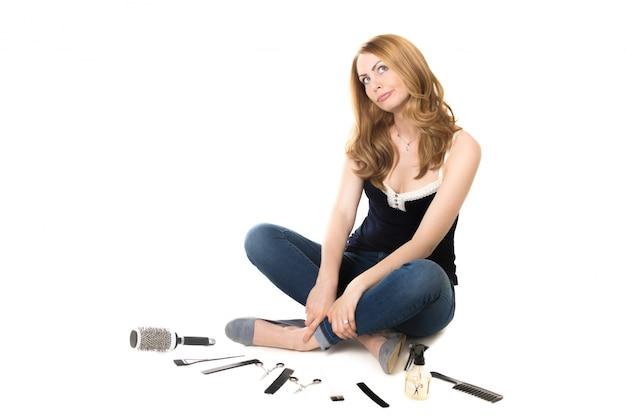 Mulher sentada no chão com objetos cabeleireiro