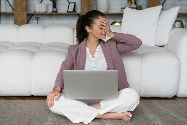 Mulher sentada no chão com um laptop no colo