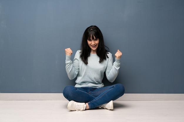 Mulher sentada no chão comemorando uma vitória na posição de vencedor
