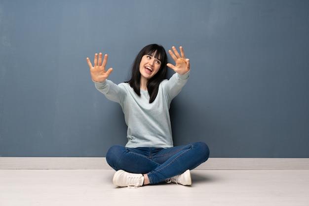 Mulher sentada no chão contando nove com os dedos