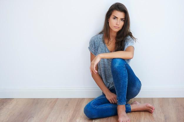 Mulher sentada no chão de madeira