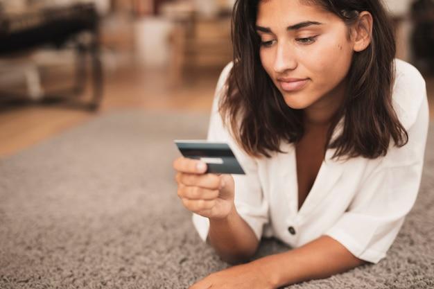 Mulher sentada no chão e olhando para um cartão de crédito