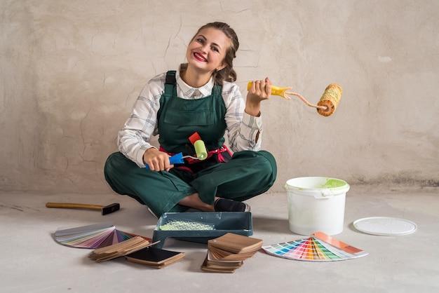 Mulher sentada no chão e posando com ferramentas de pintura