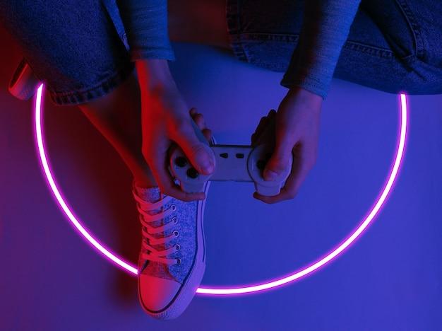 Mulher sentada no chão e segurando o gamepad. onda de sintetizador dos anos 80 e círculo brilhante retro-ondas estética futurista