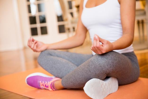 Mulher sentada no chão em casa fazendo yoga meditação