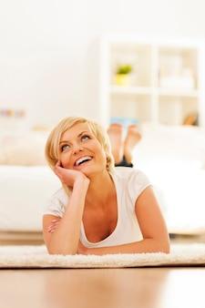 Mulher sentada no chão em casa