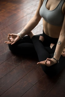 Mulher sentada no chão em pose de padmasana, fazendo o gesto de mudra