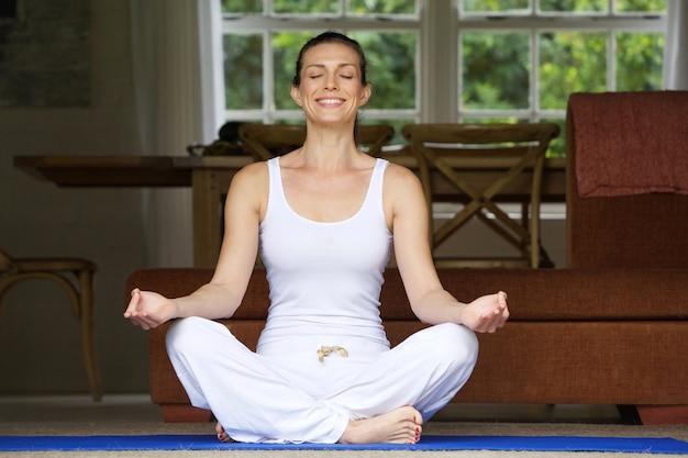 Mulher sentada no chão em posição de ioga em casa