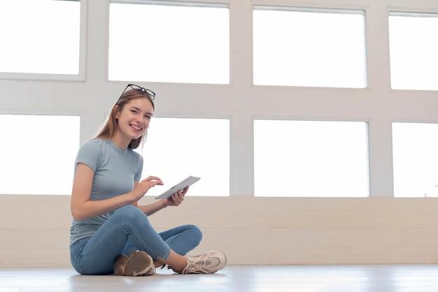 Mulher sentada no chão enquanto segura um tablet