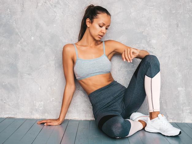 Mulher sentada no chão no estúdio perto de parede cinza