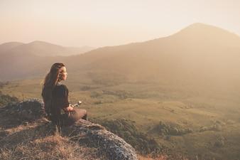 Mulher sentada no chão olhando ao pôr do sol