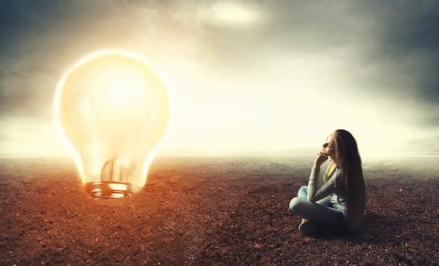 Mulher sentada no chão olhando para uma grande lâmpada, o conceito de ideia
