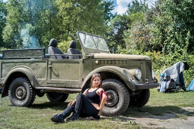 Mulher sentada no chão perto de um carro militar