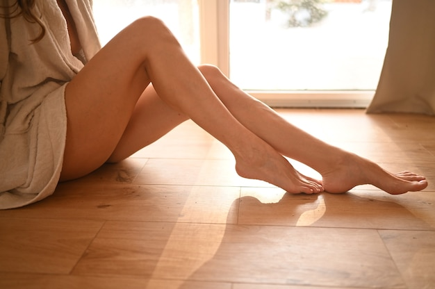 Mulher sentada no chão quente de madeira em casa dia de sol brilhante.
