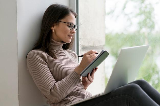 Mulher sentada no chão trabalhando em seu laptop