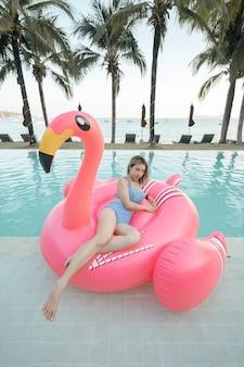 Mulher sentada no colchão inflável rosa flamingos na piscina perto da praia.