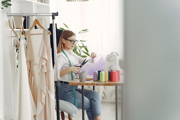 Mulher sentada no estúdio e costurar pano