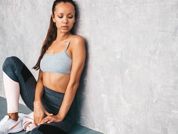 Mulher sentada no estúdio perto da parede cinza