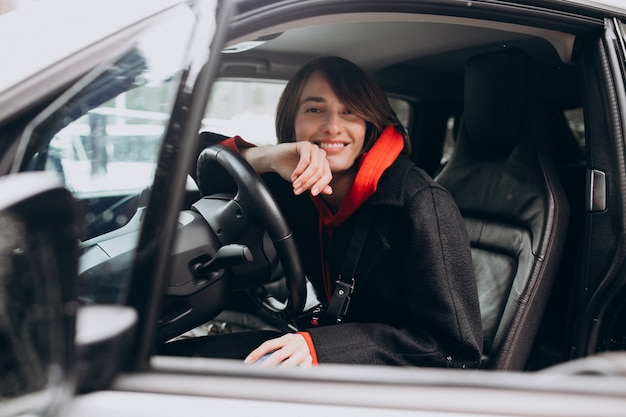 Mulher sentada no interior do carro eletro enquanto carregá-lo