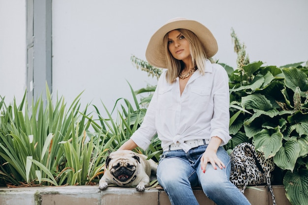Mulher sentada no parque com seu cachorro pug