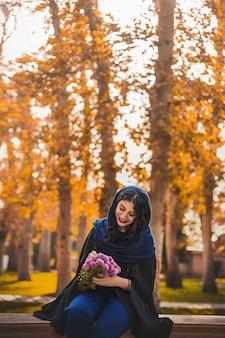 Mulher sentada no parque e segurando um buquê de flores