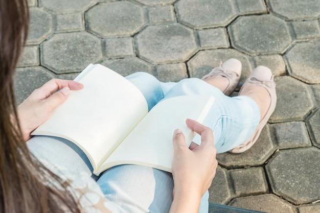 Mulher sentada no parque público para ler um livro