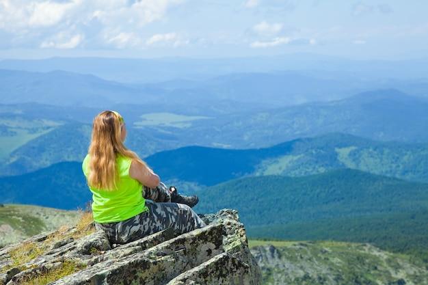 Mulher sentada no pico da montanha