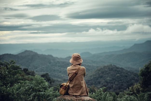 Mulher sentada no pico da montanha.