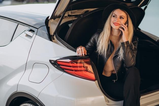 Mulher sentada no porta-malas do carro e falando ao telefone