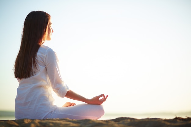 Mulher sentada no pose da ioga na praia