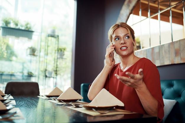 Mulher sentada no restaurante falando ao telefone