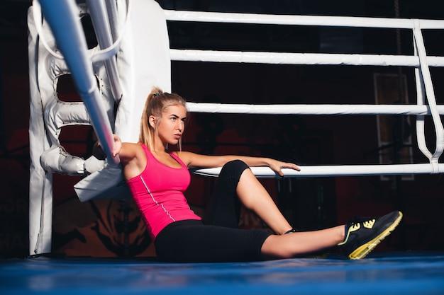 Mulher sentada no ringue de boxe